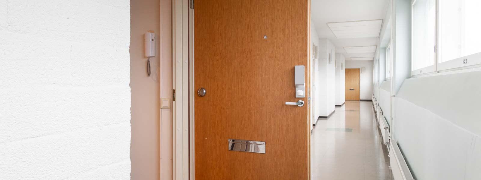 Pindora älylukko kerrostalon ovessa